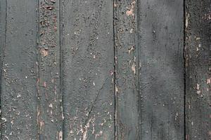 mörkgrön skalningsfärgbakgrundsstruktur. trädörr med vittrad och skalande färg foto
