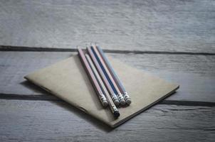 pennor med en brun anteckningsbok placerad på ett träbord foto