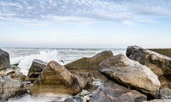 vågor som plaskar på stenar foto