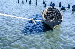grå fiskebåt bunden med ett rep i blågrönt vatten foto