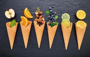 olika ingredienser för glasssmak i kottar som visar blåbär, lime, pistasch, mandel, apelsin, choklad, vanilj och kaffe på en mörk stenbakgrund. sommar- och sötmenykoncept. foto