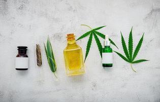 glasflaskor med hampaolja och hampablad upprättade på en konkret bakgrund foto