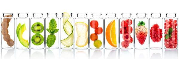 hemlagad hudvård med fruktingredienser av avokado, apelsin, blåbär, granatäpple, kiwi, citron, gurka, tamarind, jordgubbe och hallon i glasflaskor isolerad på en vit bakgrund. foto