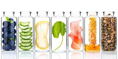 hemlagad hudvård med naturliga ingredienser och örter i glasflaskor isolerad på en vit bakgrund foto