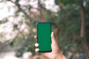 man håller telefonen utanför med grön skärm foto