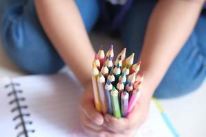 närbild av ett barns hand som rymmer många färgglada pennor foto