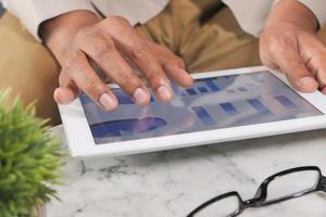mans hand som arbetar på digital tablet vid kontorsskrivbordet