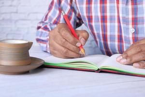 närbild av mans hand som skriver i anteckningar