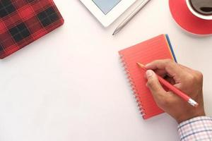 mans hand skriva på rött anteckningsblock med penna