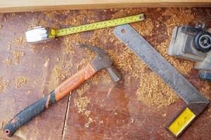 ovanifrån av snickeriverktyg på smutsigt träskrivbord med sågspån foto