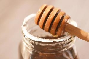 färsk honung med droppare på bordet foto