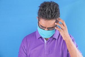 man som bär ansiktsmask med huvudvärk