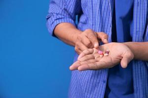 närbild av mans hand tar medicin