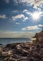 solen ovanför en stenig strand foto