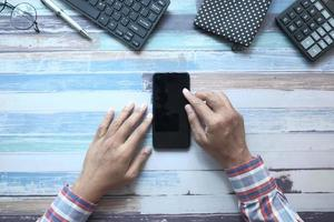 platt sammansättning av handen med smart telefon på trä bakgrund foto