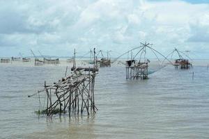 marinmålning med folkmassan av traditionella fiskeverktyg i havet med horisont i bakgrunden foto
