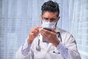läkare som använder smart telefon på sjukhuset