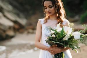 brud med en bröllopsbukett på stranden foto