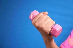 närbild av kvinna med rosa hantel på blå bakgrund