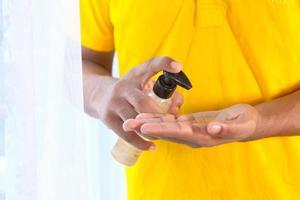 man använder handdesinfektionsmedel