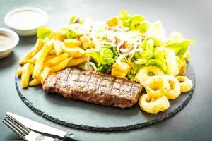 grillad nötköttbiff med pommes frites lökring med sås och färsk grönsak