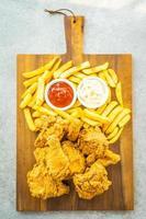 stekt kycklingvingar med pommes frites och tomat eller ketchup och majonnäs sås
