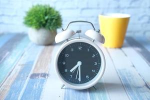 väckarklocka och gult kaffemugg på bordet foto