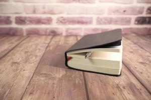 närbild på bok och penna på träbord
