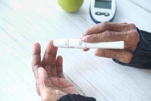 äldre kvinnor diabetiker mäter glukosnivån hemma