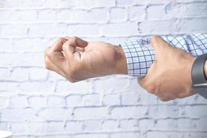 man lider av smärta i handleden på nära håll foto