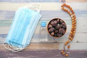 ovanifrån av handdesinfektionsmedel, ansiktsmask och färsk dadelfrukt på bordet foto