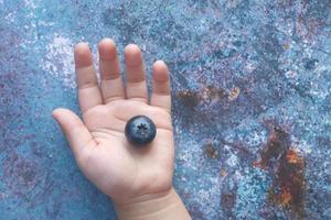 närbild av färska blå bär i barns hand