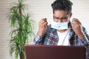 ung affärsperson som bär skyddande mask medan han arbetar på bärbar dator