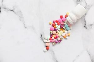 färgglada piller spilla på vit marmor bakgrund foto