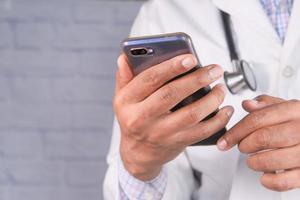 läkare i vit kappa med en smartphone