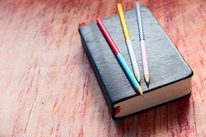 bok med pennor på trä skrivbord