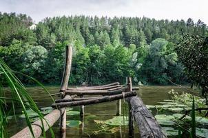 sliten brygga vid floden foto