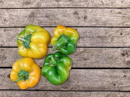 gula och gröna paprika på en träbord bakgrund foto