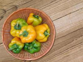 gula och gröna paprika i en flätad skål på en träbordbakgrund foto