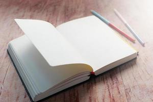 öppen bok och penna på träbord