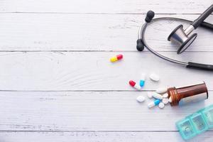 vita piller och stetoskop på vit bakgrund foto