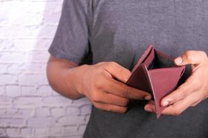 mans hand som öppnar en tom plånbok med kopieringsutrymme