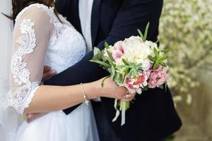bruden och brudgummen kramar foto