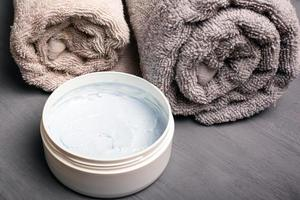 pastellfärgade rullade handdukar och kroppsskrubb på en grå bakgrundsnärbild foto