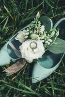 bröllopsskor med blommor och ringar foto