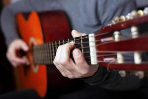 man spelar med akustisk orange gitarr foto