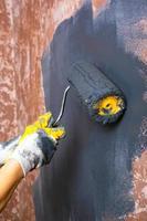 måla väggarna med en rulle i grå färg foto