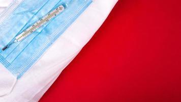 medicinsk mask och termometer på en doktors mantel på en röd bakgrund