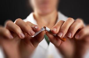 händerna på en läkare bryter en cigarett närbild foto