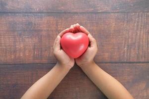 barns hand som håller rött hjärta på träbord foto